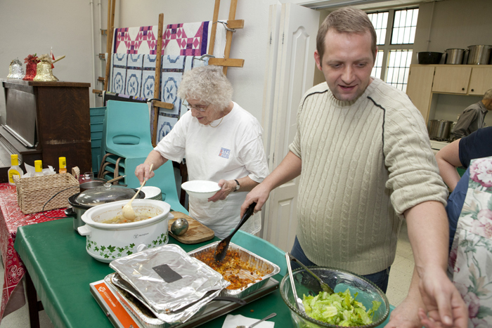 Evelyn Kidd, left, and Michael Gould, Chair of the Beach Interfaith Outreach Lunch at Kingston Road United Church serve lunch to a group of residents on Jan. 4. PHOTO: Phil Lameira / Beach Metro News