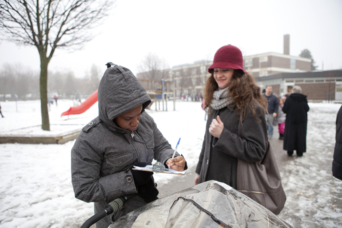 Nakesha Nelson signs a petition from organizer Swarna Banerjee. Parents gathered signatures on Jan. 28 at Secord Public School to have TDSB put the school on a priority list for funding for upgrades. PHOTO: Phil Lameira / Beach Metro News