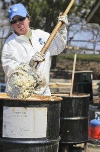 Nancy Wilson shovels a load of artificial tallow into a propane-fired drum for melting.