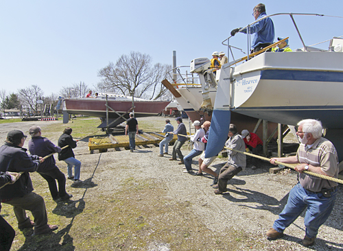 Boaters haul a cradled yacht onto a winch-powered railway that will then it carry it to Ashbridges Bay.