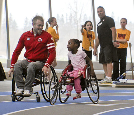 Paralympian Josh Cassidy chats with Justine Wilmot while guiding her through her first laps in a racing chair at the Whitby Athletics Centre on April 28. Behind, able-bodied members of the Durham Dragons test their strength in para-athletic style shotput.