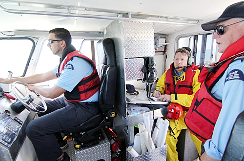 Pickering Auxiliary Rescue Association members Adrian Anwar, left, Colin Thompson and Michael Leahy, far right, prepare for a rendezvous with the 424 Transport and Rescue squadron helicopter on July 13.  PHOTO: Andrew Hudson