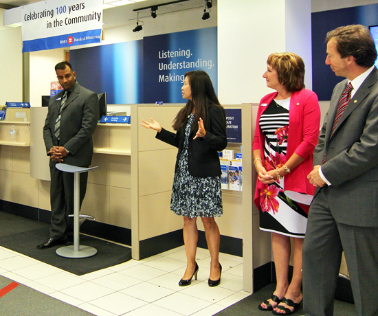 Myra Kong, branch manager at the Bank of Montreal, welcomes guests at BMO's 100th year in the Beach, at right. The branch, which has moved from its original location, held a party for customers and dignitaries to celebrate the milestone. PHOTO: Andrew Hudson