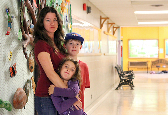 Heather Tormey stands with her son Eagan and daughter Neira inside Secord Public School on Sept. 6. A three-year effort by parents and others to have additional classrooms built at Secord stalled last fall when the province froze the capital funding budget of the Toronto District School Board. PHOTO: Andrew Hudson