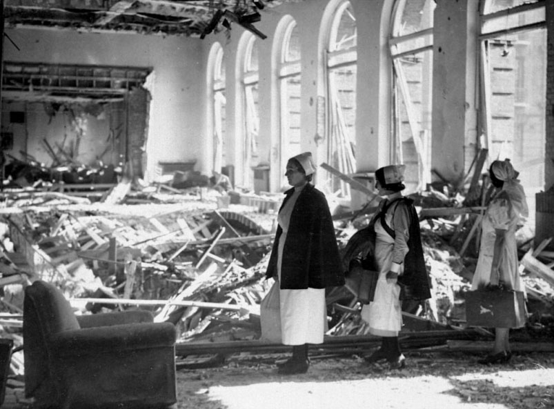 "Nurses survey bomb damage at the Manchester Royal Infirmary nurses' residence. Veteran Jean Eade was outside when she saw a buzz bomb hit the building on October 11, 1940. ""For a couple of seconds, the wall was there, and then – it was like a movie,"" she said. ""The wall came out and you could see all the rooms.""  Photo courtesy Central Manchester University Hospitals NHS Foundation"