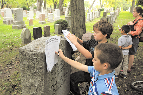 Isaac, front, and Jeremy consult their checklists during a scavenger hunt at St. John's Norway Cemetery on Sept. 15.  PHOTO: Jon Muldoon