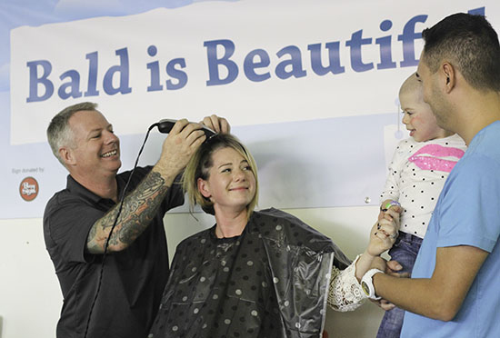 Stephanie Reid has her hair shaved Sept. 29 in solidarity with her two-year old daughter Keaton, at right, who has leukemia. For more information, visit kissesforkeaton.com. PHOTO: Andrew Hudson
