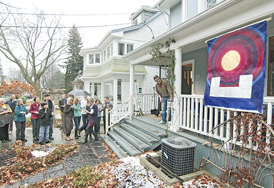 Artist Benedict Hilliard reveals the first of 25 holiday flags on Leuty Avenue on Dec. 1. Residents on the street reveal a new 'advent' flag each day leading to Christmas, which are then auctioned off to raise money for the Daily Bread Food Bank. PHOTO: Andrew Hudson
