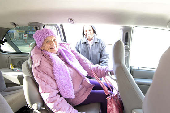 "Neighbourhood Link driver Alem Abebe helps Rena into the ""Neighbourhood Link limo"" at the Adult Day Program. Rena is one of hundreds of seniors who take advantage of the organization's ride service in the East End. PHOTO: Jon Muldoon"