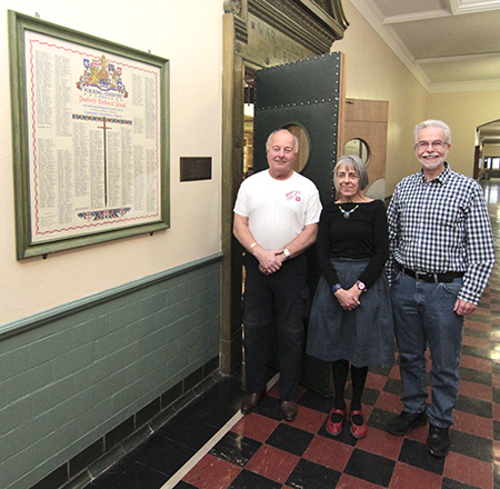 Danforth Tech alumni Bryan Bennett, left, and Ron Passmore, right, stand with librarian Barbara MacKay outside Danforth Collegiate and Technical Institute's War Memorial Library on Jan. 15. To celebrate the school's 90th anniversary, the Danforth Tech Society will better preserve 1,600 letters and 400 postcards, such as the one pictured, below, mailed to the school by Danforth students, graduates and teachers who volunteered for active service in the second world war. At left, above, is one of four hand-lettered rolls listing the more than 2,200 volunteers. PHOTO: Andrew Hudson