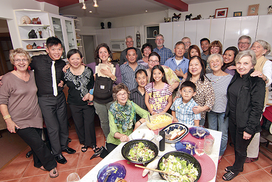 Enjoying a reunion dinner with some of the Beach families who sponsored their settlement in Toronto are Anh Giang, third from left, Minh Giang, kneeling, Manh Giang, wearing a solid blue shirt at centre, and Thu Dao Tren, wearing the leopard print shirt at right. PHOTO: Andrew Hudson