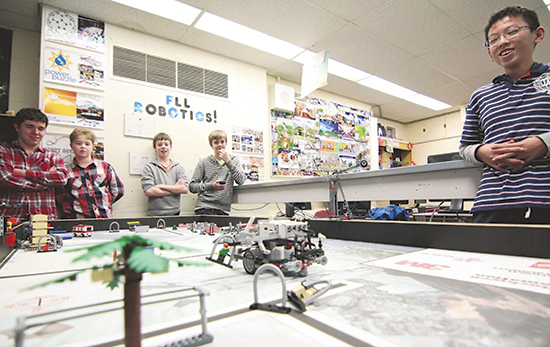 Glen Ames graduate Gregor Browning, left, watches with some of the Grade 7 and 8s on the school's current robotics team as their typhoon-fighting LEGO robot rescues a human figure in practice run before the provincial FIRST LEGO League tournament in Oshawa on Jan. 18. Glen Ames came first among the 32 Toronto schools competing at a qualifier for a spot at provincials this year, an achievement based on their near-perfect robot challenge and a typhoon education campaign during which they raised more than $3,000 and 17 boxes of supplies for a school hit by Typhoon Haiyan in the Philippines. PHOTO: Andrew Hudson