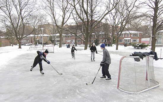 From left, Malvern students Austin, Jacob, Marshall and Jake play shinny on the Love Crescent Parkette rink on Dec. 19. At left, the volunteers who spray, flood, shovel and scrape the rink into shape take a timeout for a team photo. PHOTO: Andrew Hudson