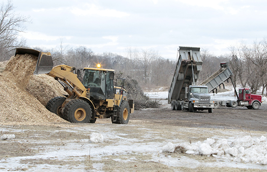 Workers pile brush and woodchips collected after the December ice storm on the old quarry lands at Victoria Park Avenue and Gerrard Street East. PHOTO: Andrew Hudson