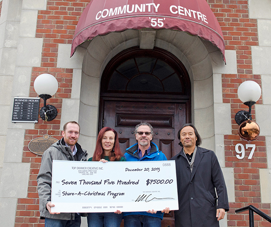 Debbie Visconti, centre, executive director of Community Centre 55, accepts a cheque for $7,500 from representatives of Top Drawer Creative Inc., including account director Chris Jones, vice president and creative director Brian Gahan and president Howard Chang. The Beach-based agency is behind the Beach Village BIA rebranding campaign, and charged a discounted fee which was donated to Centre 55's Share A Christmas campaign. PHOTO: Jon Muldoon