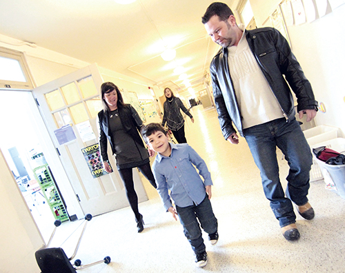 Six year-old Hercules Stergiou, who has cerebral palsy, walks without his walker down the hallway to his Grade 1 class at Bowmore Public School. Beside him are his parents Jim and Kristina, while his principal Thelma Sambrook shouts her support from behind. Sambrook wrote a picture book, called All About Me – Hercules, that tells the story of his year in kindergarten. Published by the Toronto District School Board, $3 from the sale of each book will go to support SickKids Hospital. PHOTO: Andrew Hudson