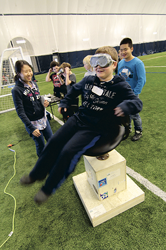Phoebe Yung, a Grade 11 student at Monarch Park Collegiate, takes students from Westwood Middle School for a spin in a chair modelled on astronaut training exercises. Spinning upsets the vistibular system – three fluid-filled canals in the inner ear that give people a sense of balance. PHOTO: Andrew Hudson