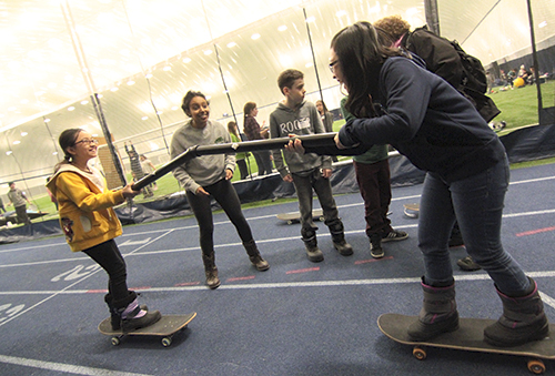 Elizabeth Ambachew, a Grade 12 volunteer from Monarch Park Collegiate, watches as Leslieville Elementary students Lucy, left, and Yeon, right, try and fasten together a pair of PVC pipes while balancing on skateboards. PHOTO: Andrew Hudson