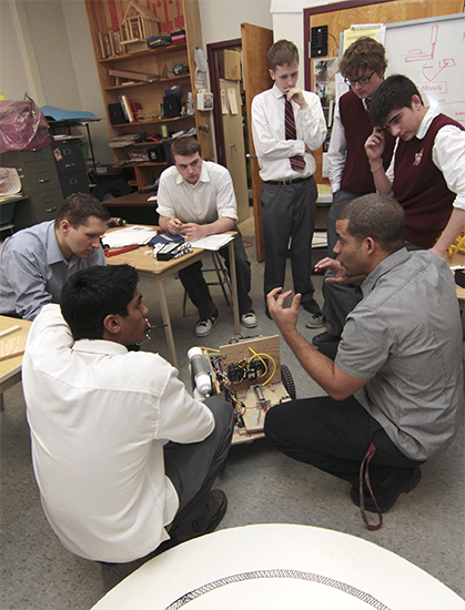 Students in the Neil McNeil robotics club listen to teacher and assistant robotics coach Jason Milne, bottom left, with just a few days to go before this year's TCDSB robotics contest. This year's robots had to load and shoot hockey pucks on a large-scale crokinole board. PHOTO: Andrew Hudson