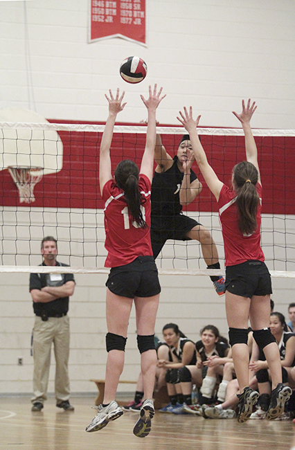 Andy Phan, co-caption of Danforth Collegiate's co-ed volleyball team, spikes the ball over North Toronto's formidably tall blockers at a May 1 home game. The game went a full five sets before Danforth secured a win. Heading into playoffs later this month, Danforth and North Toronto are the two top-ranked co-ed teams in south Toronto. PHOTO: Andrew Hudson