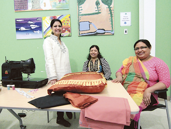 "From left, Lucky Nessa, Protima Sarker, and Jamee Ara Hosne of the Dunia Design Collective at the AccessPoint community centre on Danforth Avenue.  From everyday shirts and skirts to laptop covers, pillows, even wedding dresses, the women at Dunia Design Collective can design and sew it all.  Designer Lucky Nessa described the group's style as a hybrid of contemporary Western and Bangladeshi styles. While they show finished pieces at craft fairs and community events, most of Dunia's work is custom-made. Working Saturdays from the AccessPoint centre at Danforth and Victoria Park, all the women in the three year-old collective learned to design and sew in Bangladesh. Home to some of the world's best cotton, and muslin so fine that ""a whole saree can pass through a ring,"" Bangladesh also has a strong tradition of home designers that has the effect of turning thousands of families into competing fashion houses. To learn more or to place an order, email duniacollective@gmail.com. PHOTO: Andrew Hudson"