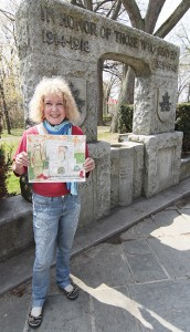 Beach artist Jennifer Cline displays her painting of the Kew Gardens war memorial. The painting will be sold to the highest bidder, with the funds going to a restoration of the cenotaph, along with adding names to recognize Canadian soldiers' more recent contributions in peacekeeping missions and conflicts. PHOTO: Andrew Hudson