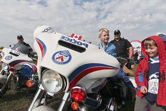 From left, Tristan and Callum, both six years old, check out Toronto police officer Andrew Hong's motorcycle at the Police Week community fair held on May 21 in Woodbine Park. Hong, who patrols roads and highways, escorts VIPs and handles speeding complaints with the Traffic Motor Squad, said the bike is a brand-new Harley Davidson Police Special with a 1700cc engine. PHOTO: Andrew Hudson