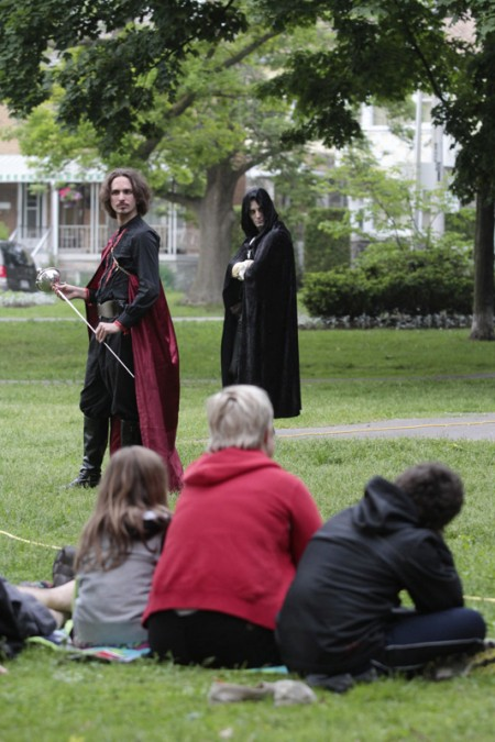 Sword drawn, the villain Iago (played by James Soares-Correia) plots while the disguised Roderigo (Jonathan Dufour) looks on during the opening night performance on June 11 in Norwood Park. PHOTO: Andrew Hudson