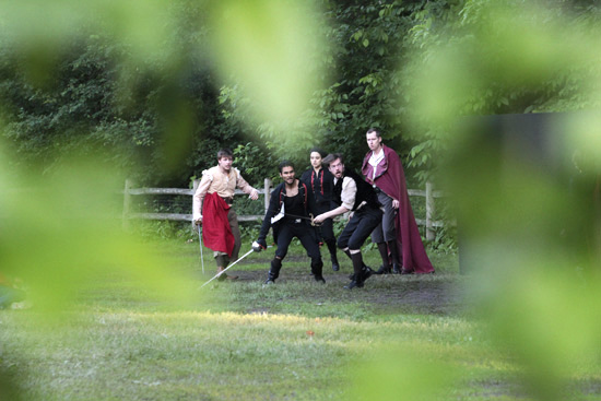 Othello (played by David Chinchilla) breaks up a sword fight between his red-caped lieutenant Cassio (Mikhael Melnikoff) and Montano (Vince Deiulis) during Bard in the Park's June 15 performance of Othello at Kew Gardens. PHOTO: Andrew Hudson