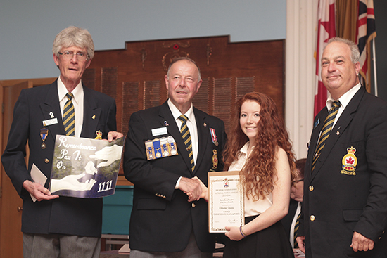 Notre Dame student Christine Devine receives an award for her winning Remembrance Day poster design from District Commander Jay Burford, centre, Baron Byng Legion Youth and Education Coordinator Michael Hornby, left, and Baron Byng Legion President Gerry Morgan, right at the Gerrard and Coxwell Avenue legion on June 11. Devine's poster, a copy of which is held by Michael Hornby at left, shows the hand of one generation passing a poppy to another. PHOTO: Andrew Hudson
