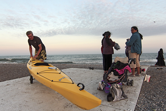 "Mark Kremblewski wheels his kayak home at sunset last Saturday using a new pathway that parks staff installed earlier this month at Woodbine Beach. ""It's very difficult to wheel on the sand, so having this come right to the water is fantastic,"" he said, adding that the path is already a hit for families with strollers and early-morning walkers who don't want sand in their shoes. PHOTO: Andrew Hudson"