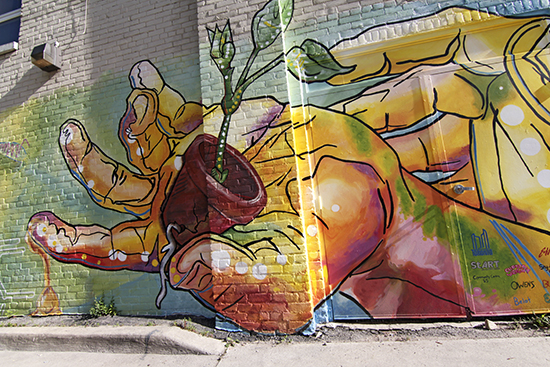 A detail of 'Bee Haven,' a new mural painted by artists Elie Saad, Sarah Van Duesen, and Curtia Wright together with youth from Community Centre 55: Ben Owens, Conor Belot, Sarah Buckner, and Shy-Anne Lights. With support from StreetARToronto, the mural at the back of Danforth Avenue's Dixon Hall is part of a local couple's project to turn the alley between Danforth and Coleman into an Alleyway of Dreams.