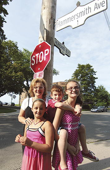 From left, Susan Forrest stands with her children Isobel, Eddy, and Olivia under a new stop sign that was installed at Hammersmith and Hubbard Avenues after their successful petition this winter.  PHOTO: Andrew Hudson