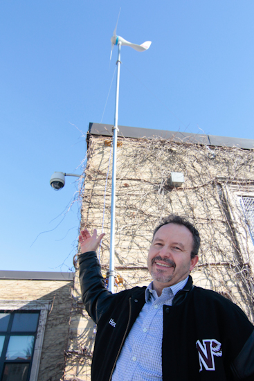 Neil McNeil High School teacher Joe Ferro shows the new wind turbine installed above the school's technology class this fall. PHOTO: Andrew Hudson