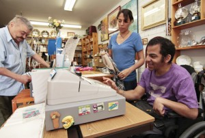Chris, a Pegasus participant, rings up the till for a customer while staffer Rose Leask looks on. At the Pegasus thrift store on Kingston Road, participants gain work experience while helping raise funds for the program. PHOTO: Andrew Hudson