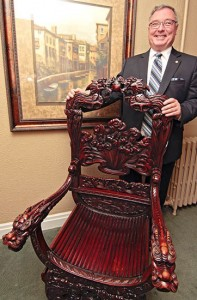 Nick Larter, funeral director at Sherrin Funeral Home, stands by the antique chair that will continue to be a Beach conversation piece when it moves to the Williams cottage in Kew Gardens. PHOTO: Andrew Hudson