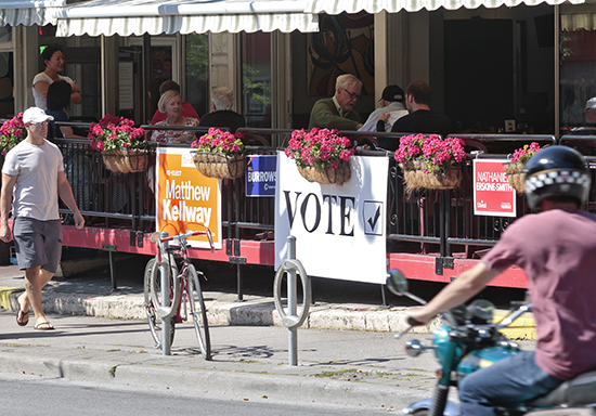 Election signs are sprouting up across the country, though some establishments, like the Beacher café, allow space for all candidates, alongside a message encouraging passerby on Queen Street East to take the time to vote in the Oct. 19 federal election. PHOTO: Andrew Hudson