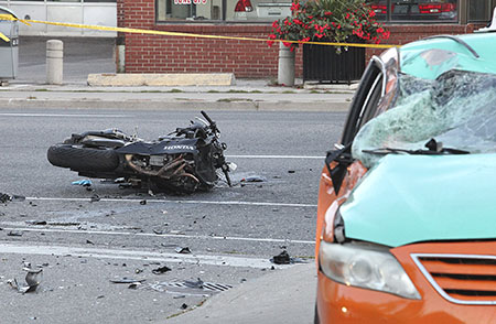 A major collision involving a motorcycle and a Beck taxi cab closed Danforth Avenue from Victoria Park Avenue to Pharmacy Avenue on the evening of Saturday , Sept. 26 while officers reconstructed the scene.  PHOTO: John Hanley