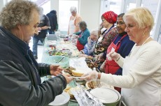 Beach United Church volunteer Marcha Armstrong, right, dishes out Lebanese food during the church's Interfaith drop-in lunch Feb. 5.