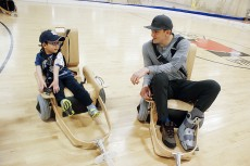 "Liam Marriage, 5, shows Toronto Maple Leafs forward James van Riemsdyk how to make moves on Variety Village's new volt hockey chairs. One move was a quick spin and stop, which he hadn't named yet. The other, called ""the worm,"" saw him squiggle across the court."