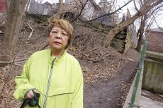 Joan Eskins with the retaining wall she's been ordered to repair or replace at her recently-purchased Beach Hill home.
