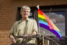 Dean Will outside of his home June 21. He's attached rose branches to his Pride flag to detract people from stealing it.