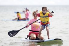 Frankie Barbera, 9, is all smiles with instructor Jana Ruby at the fifth annual Aloha Toronto held at Balmy Beach on August 21. Founded by beacher Helen Hatzis, Aloha Toronto has children with Autism Spectrum Disorders participate in surfing and paddleboard workshops throughout the day as a form of relaxation and fun.