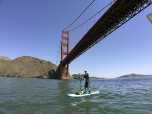 Markus Pukonen stand-up paddleboards under San Fransisco's Golden Gate Bridge. PHOTO: Routes of Change